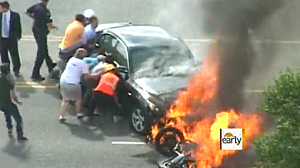 People lift flaming Car